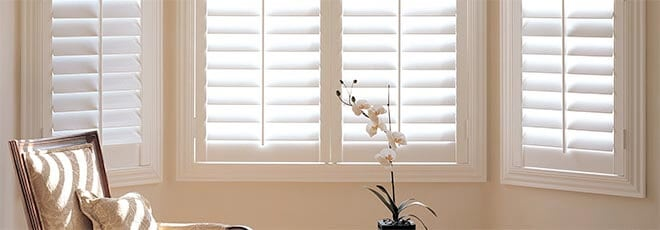 Interior shutters Austin Texas composite shutters installers beautiful white shutter vertical windows living room flower chair shade and sun