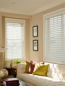 window blinds austin texas norman blinds performance faux wood blinds living room windows white blinds photo frames coffee table throw pillows vase books end table fire place cream walls