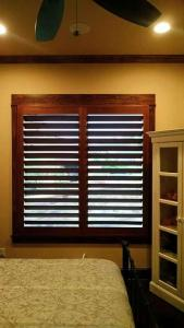 austin texas window shutters by shades of texas dark brown colored shutters large window bedroom bed carpet lights ceiling fan